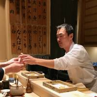 Personal touch: Chef Toshiyuki Suzushi hands a customer freshly made tempura at his Sonoji restaurant. | ROBBIE SWINNERTON