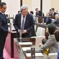Kumamoto Municipal Assembly member Yuka Ogata holds her 7-month-old baby as her colleagues try to persuade her to leave the chamber in November. | KYODO
