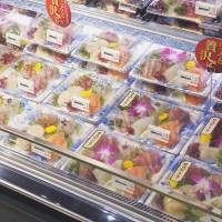 Sashimi is displayed in recycled food trays. | FP CORP.