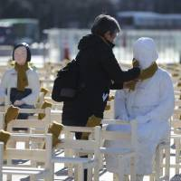 A woman in Seoul on Dec. 27 puts a scarf on a statue in an installation symbolizing 'comfort women.' The following day, South Korean President Moon Jae-in said the country's 2015 agreement with Japan to settle the decadeslong impasse over the issue was seriously flawed. | AP