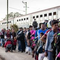 Large numbers of migrants transit through the city of Zakany in Hungary on their way to seek work in Germany and other European nations in 2015. | GETTY IMAGES