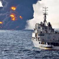 A rescue ship sails near the burning Iranian oil tanker Sanchi in the East China Sea off the eastern coast of China on Sunday. | AP