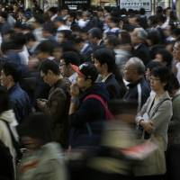 Commuters crowd a train station in Tokyo. Japan's working-age population is forecast to shrink by about 20 million between now and 2050 — a number equivalent to roughly 30 percent of the nation's current workforce. | BLOOMBERG