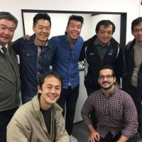 Serving the community: President Arthur Muranaga (left) and Jhony Sasaki (center) pose with some of the IPC team at the firm's offices in Tokyo's Chuo Ward. | COURTESY OF IPC WORLD INC.