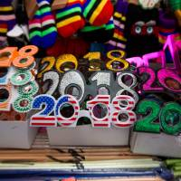 Pairs of 2018 glasses sit on display for sale in a vendor's booth ahead of New Year's Eve celebrations in the Times Square area of New York City on Dec. 30. | BLOOMBERG