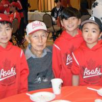 Former Vancouver Asahi player Koichi Kaminishi poses with children during an event earlier this month. | KYODO