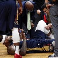 New Orleans center DeMarcus Cousins lies on the court while being tended to after injuring his left Achilles tendon, according to the team, during the second half of Friday's game against Houston. | AP