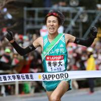 Aoyama Gakuin University anchor Takaya Hashima crosses the finish line to claim victory for his team in the Tokyo-Hakone collegiate men's ekiden on Wednesday. | KYODO
