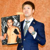 Kosei Tanaka holds up a photo of Filipino Ronnie Baldonado, his opponent for a March 31 bout in Nagoya. Tanaka will make his flyweight debut in the fight. | KYODO