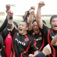 The Hino Red Dolphins celebrate their 20-17 victory over the NTT Docomo Red Hurricanes in the Top League relegation-promotion playoffs on Saturday in Osaka. | KYODO