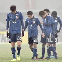 Japan's players trudge off the pitch after losing 4-0 to Uzbekistan on Friday in the quarterfinals of the AFC Under-23 Championship in Jiangyin, China. | KYODO