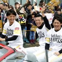 SoftBank players (from left) Nao Higashihama, Kodai Senga and Takuya Kai particpate in the team's victory parade in on Nov. 26, 2017. | KYODO