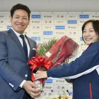 A Seibu Lions team official presents Kazuhisa Makita with flowers during a news conference at the team office on Wednesday. Makita is leaving the Lions to join the San Diego Padres in MLB for the 2018 season. | KYODO