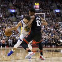 Warriors guard Stephen Curry is defended by the Raptors' DeMar DeRozan during the second half on Saturday in Toronto. | AP