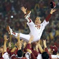 Senichi Hosono, who died Thursday after a battle with pancreatic cancer, is tossed into the air by members of the Rakuten Eagles after the team won the Japan Series in November 2013.   KYODO