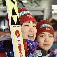 Yuki Ito speaks into a microphone as Sara Takanashi listens after a World Cup ski jumping event in Yamagata on Sunday. | KYODO