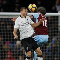 Liverpool's Ragnar Klavan (left) vies for the ball with Burnley's Ashley Barnes in Premier League action on Monday. | REUTERS