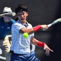 Yuichi Sugita hits a return against Ivo Karlovic during the second round of the Australian Open on Wednesday in Melbourne, Australia. | AFP-JIJI