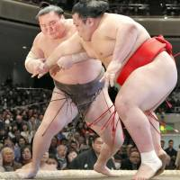 Yokozuna Hakuho (left) grapples with Onosho  during the first day of the New Year Grand Sumo Tournament on Sunday at Ryogoku Kokugikan. | KYODO