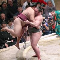 Tochinoshin lifts Mitakeumi out of the ring at the New Year Grand Sumo Tournament at Ryogoku Kokugikan on Monday. | KYODO