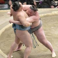 Tochinoshin (right) grapples with Tamawashi during a New Year Grand Sumo Tournament match on Thursday at Ryogoku Kokugikan. | KYODO