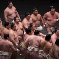 Sumo wrestlers rush to be picked next by Tochinoshin (far right) in a winner-stays-on training match in April 2016. | JOHN GUNNING