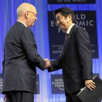 Prime Minister Shinzo Abe and World Economic Forum founder and Executive Chairman Klaus Schwab shake hands at the 'The Reshaping of the World: Vision from Japan' session at the WEF annual meeting on Jan. 22, 2014. | SWISS-IMAGE.CH