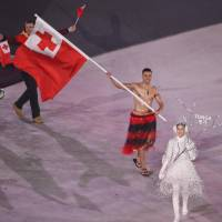 Pita Taufatofua of Tonga carries the national flag in the opening ceremony. | REUTERS