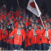 Noriaki Kasai of Japan carries the national flag during the opening ceremony. | REUTERS
