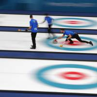 Italy delivers a stone during the Italy v Denmark men's round robin curling match at the Gangneung Curling Center. | REUTERS
