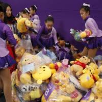 Olympic staff gather Pooh bears thrown by fans following the short program performance of Yuzuru Hanyu.  | REUTERS