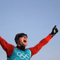 Dario Cologna of Switzerland celebrates after winning his third straight Olympic gold medal in the men's 15km individual on Friday. | REUTERS