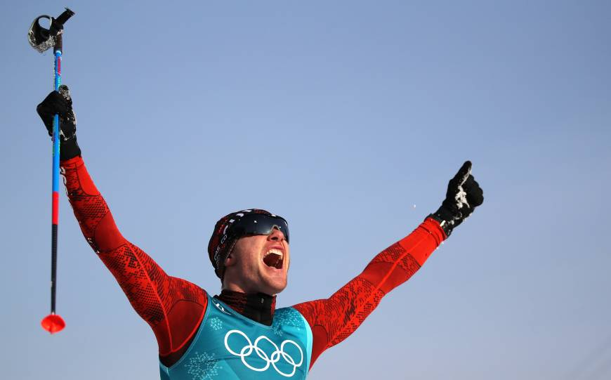 Dario Cologna of Switzerland celebrates after winning his third straight Olympic gold medal in the men