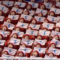 North Korean cheerleaders hold unification flags as they attend the pair skating free skating of the figure skating event on Friday.  | AFP-JIJI