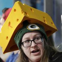 A spectator wears a Green Bay Packers cheese hat during the men's curling matches. | AP
