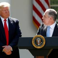 U.S. President Donald Trump listens to EPA Administrator Scott Pruitt after announcing his decision that the United States will withdraw from the Paris Climate Agreement, in the Rose Garden of the White House in Washington last June. | REUTERS