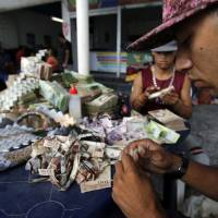 Venezuelan family recycles worthless piles of bolivar bills into crafts and origami