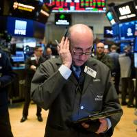 Traders work on the floor of the New York Stock Exchange (NYSE) on Monday. U.S. stocks remained down after recovering from steeper early losses, while European and Asian equities slumped. | BLOOMBERG