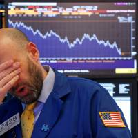 A trader reacts near the end of the day on the floor of the New York Stock Exchange Thursday. | REUTERS