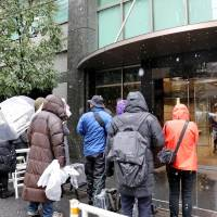 Reporters gather in front of the building that houses Coincheck Inc's office in Shibuya, Tokyo, last week as the Financial Services Agency conducts an on-site inspection. | KYODO