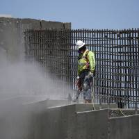 A man works on the Southern Nevada portion of U.S. Interstate 11 near Boulder City, Nevada, last May. President Donald Trump's $1.5 trillion infrastructure proposal fulfills a number of campaign goals, but relies heavily on state and local governments to produce much of the funding. | AP