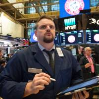 A trader works on the floor of the New York Stock Exchange on Feb. 5 after a brutal trading session. | AFP-JIJI
