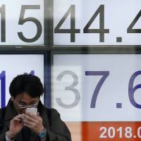 A man looks at a mobile phone in front of an electronic board showing the Nikkei average outside a brokerage in Tokyo on Tuesday morning. | REUTERS