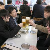 People hold a toast after work at a bar in Tokyo's Shibuya district on Friday afternoon. | KYODO