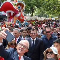 Australian Prime Minister Malcolm Turnbull takes a selfie as he walks with Victorian Premier Daniel Andrews and members of the public during a parade as part of the Chinese New Year Festival in Melbourne, Australia, Sunday. | AAP / DAVID CROSLING / VIA REUTERS