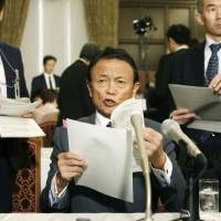 Finance Minister Taro Aso speaks to reporters on Friday in Tokyo. | KYODO
