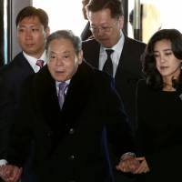 Lee Kun-hee, chairman of Samsung Electronics Co., center, and daughter Lee Boo-jin, chief executive officer of Hotel Shilla Co., right, arrive for a company meeting at the Shilla Hotel in Seoul, South Korea, in January 2014. Lee Kun-hee was named on Thursday by South Korean police as a suspect in a $7.5 million tax evasion case. | BLOOMBERG