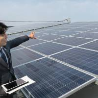 An employee of Daiwa House Industry Co. presents solar panels on the roof of the firm's new self-powered office building in the city of Saga. | KYODO
