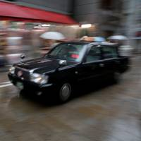 A taxi moves through an Osaka shopping district in October. Sony plans to team up with taxi operators around Japan this spring to develop an artificial intelligence-based ride-hailing system. | REUTERS
