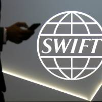A man using a mobile phone passes the logo of global secure financial messaging services cooperative SWIFT at the SIBOS banking and financial conference in Toronto in October 2017. | REUTERS